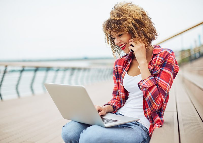 Young woman sitting at the stairs, working on laptop and talking on mobile phone