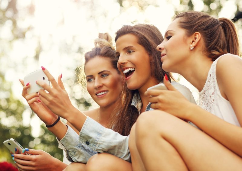 Picture showing group of girlfriends using smartphone outdoors