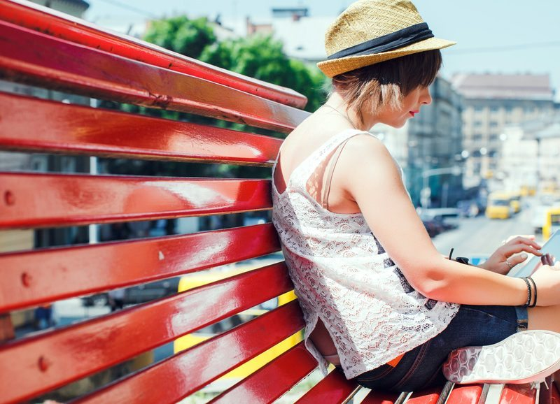 City stylish hipster tourist young woman, sitting on a red bench, using digital tablet.
