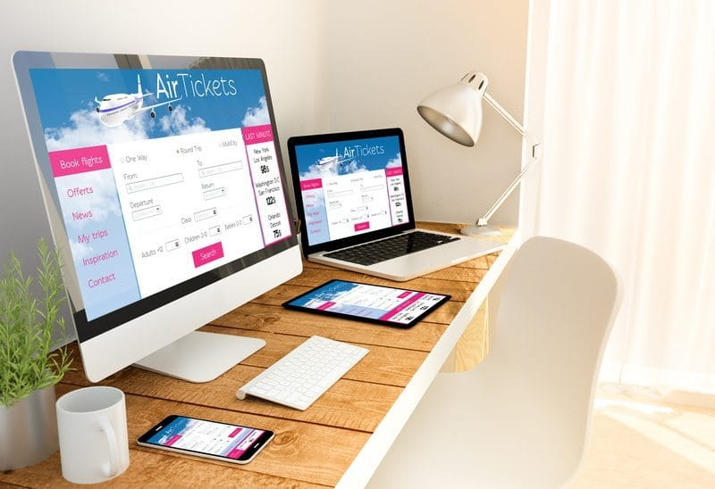 Digital generated devices over a wooden table with made up responsive ticket flight website. All screen graphics are made up.